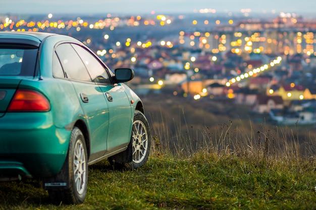 Nowoczesny samochód z niewyraźne jasne światła miasta za