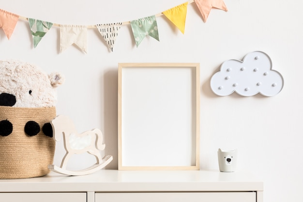 Nowoczesny skandynawski pokój noworodka z makietą ramki na zdjęcia, drewnianym samochodem, pluszowymi zabawkami i chmurkami. wiszące bawełniane flagi i białe gwiazdki. minimalistyczne i przytulne wnętrze z białymi ścianami.