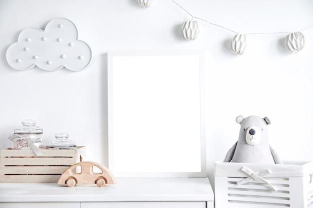 Nowoczesny skandynawski pokój noworodka z ramką na zdjęcia, drewnianym autem, pluszowymi zabawkami i chmurkami. wiszące bawełniane flagi i białe gwiazdki. minimalistyczne i przytulne wnętrze z białymi ścianami.