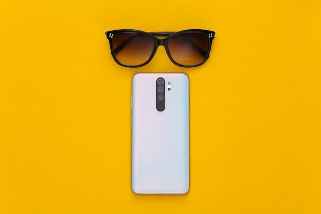 Nowoczesny smartfon i okulary przeciwsłoneczne na żółto