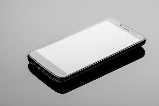 Nowoczesny smartfon na ciemnej błyszczącej powierzchni z odbiciem