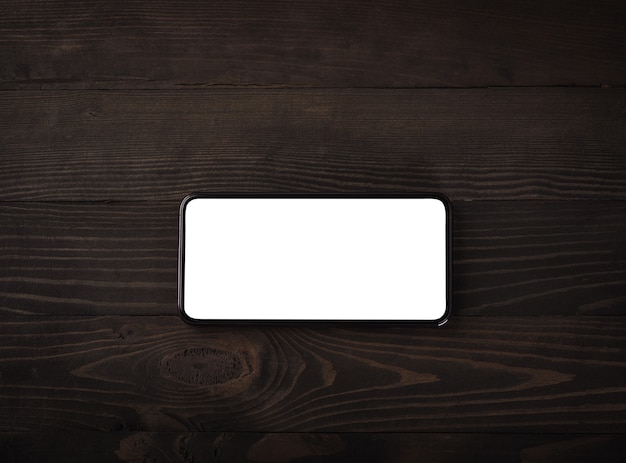 Nowoczesny smartfon na stole z czarnego drewna