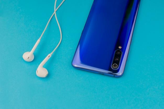 Nowoczesny smartfon z muzycznymi słuchawkami na niebieskiej ścianie