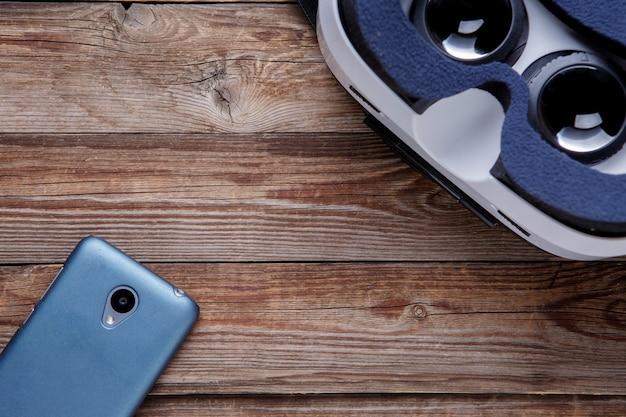 Nowoczesny smartfon z pustym ekranem i goglami wirtualnej rzeczywistości