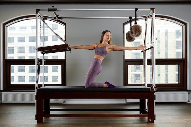 Nowoczesny sprzęt cadilac reformer do pilates na siłowni, koncepcja zdrowia i rehabilitacji, instruktor wykonuje ćwiczenia na reformerze w celu korekcji układu mięśniowo-szkieletowego.