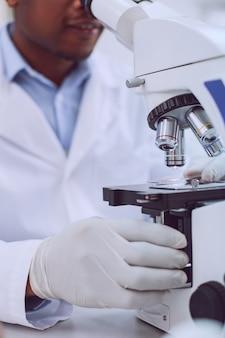 Nowoczesny sprzęt. inteligentny, profesjonalny badacz pracujący i dotykający swojego nowoczesnego, wyrafinowanego mikroskopu
