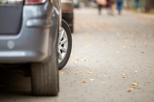 Nowoczesny srebrny samochód zaparkowany na utwardzonej słonecznej spokojnej podmiejskiej ulicy w słoneczny dzień.