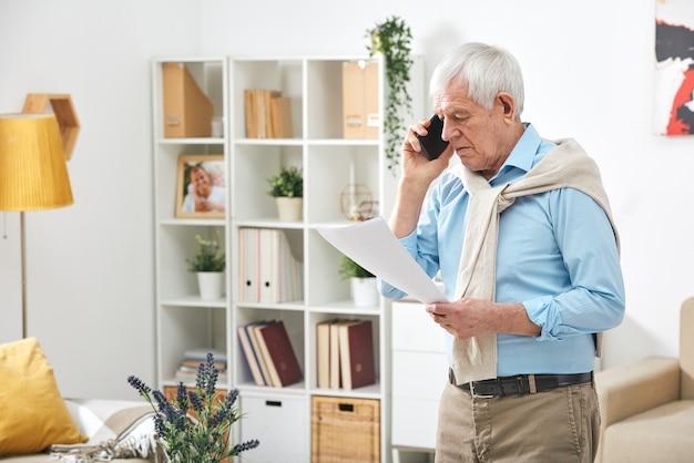 Nowoczesny starszy mężczyzna chodząc po salonie i dzwoniąc do menedżera w sprawach dotyczących dokumentów