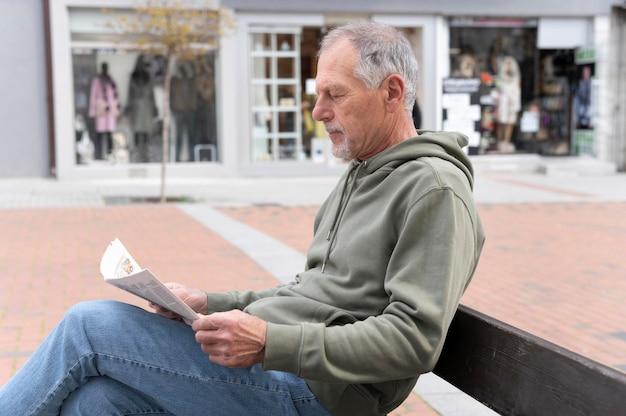 Nowoczesny starszy mężczyzna czyta gazetę