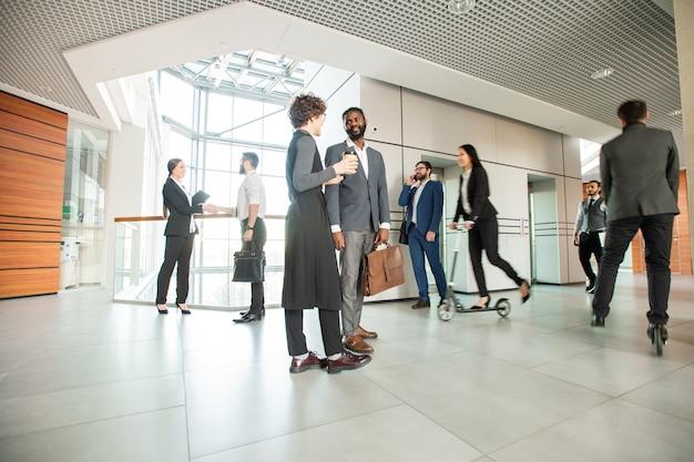 Nowoczesny styl życia w biurze: ludzie biznesu rozmawiają i chodzą, podczas gdy ich koledzy jeżdżą na skuterach po przestronnym korytarzu