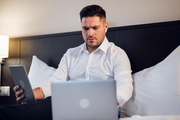 Nowoczesny styl życia zawodowy. poważny skoncentrowany mężczyzna siedzi na łóżku w domu, pracuje na laptopie online i korzysta z internetu
