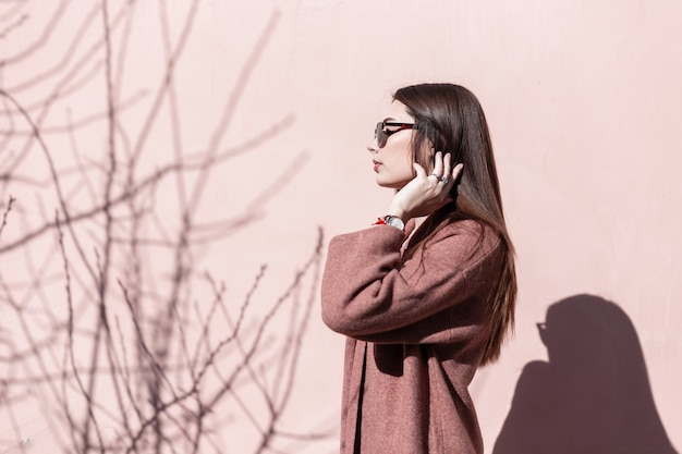 Nowoczesny stylowy piękna młoda kobieta w modnych okularach przeciwsłonecznych pozowanie stojąc w słońcu w pobliżu różowej ściany w mieście. elegancka seksowna dziewczyna w stylowym noszeniu prostuje luksusowe długie włosy. moda retro.