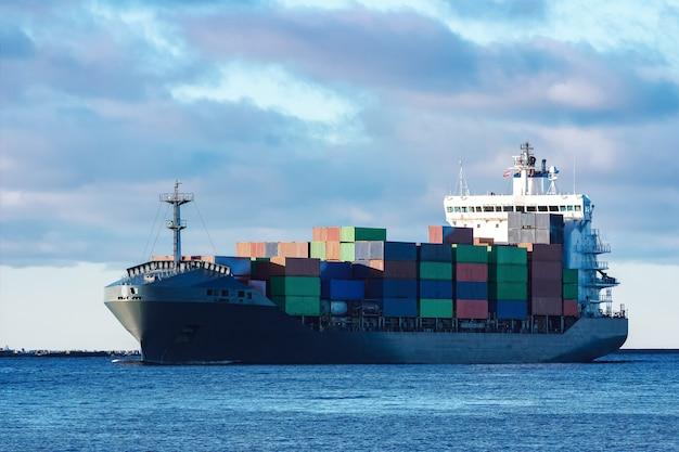 Nowoczesny szary kontenerowiec poruszający się w wodzie stojącej