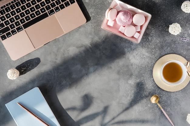 Nowoczesny szary stół na biurko z laptopem i innymi materiałami z filiżanką herbaty