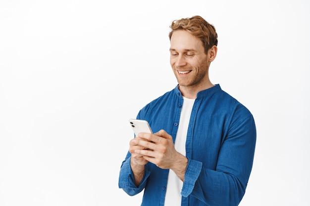 Nowoczesny szczery facet z telefonem w rękach, rozmawiający, wysyłający wiadomości lub czytający ekran, uśmiechający się do wyświetlacza smartfona podczas korzystania z aplikacji, stojący nad białą ścianą