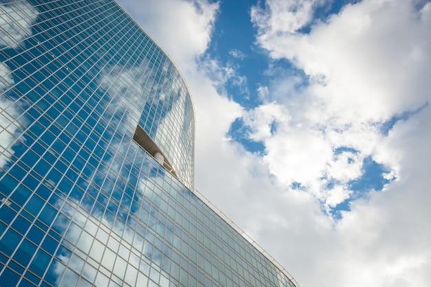 Nowoczesny szklany wieżowiec wieżowiec nad błękitnym, jasnym niebem z chmurami