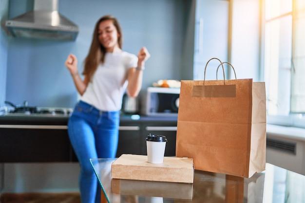 Nowoczesny taniec uradowany zadowolony radosny dorywczo dorosły szczęśliwa młoda kobieta klient otrzymał kartonowe torby z jedzeniem i napojami na wynos w domu. koncepcja usługi szybkiej dostawy