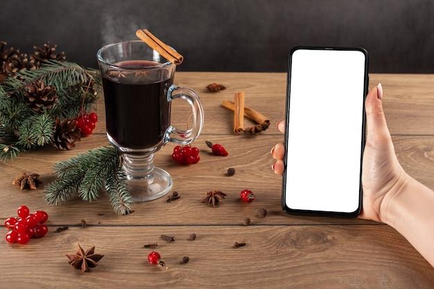 Nowoczesny telefon komórkowy z białym pustym ekranem w rękach kobiety w tle