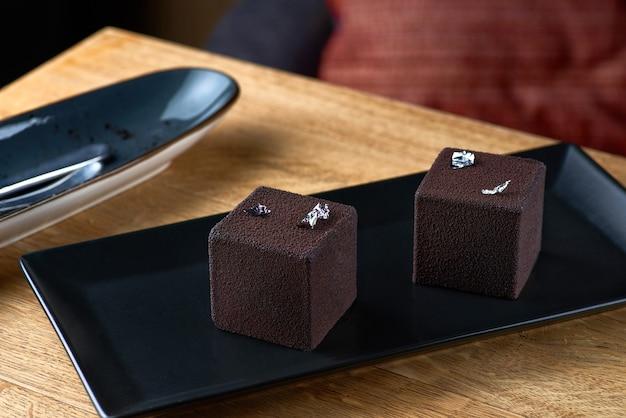 Nowoczesny tort musowy pokryty czekoladowym welurem. deserowe dania kuchni francuskiej na stole, serwowane w restauracji