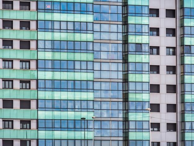 Nowoczesny wieżowiec z niebieskimi i zielonymi oknami