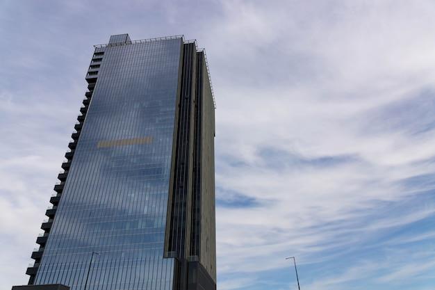 Nowoczesny wysoki biurowiec na tle nieba, wieżowiec.