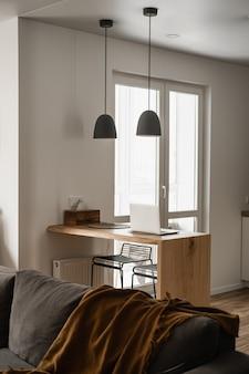 Nowoczesny wystrój wnętrz. stylowy jasny salon ozdobiony wygodną sofą, pledem, stojakiem z litego drewna, lampami wiszącymi, laptopem, białymi ścianami