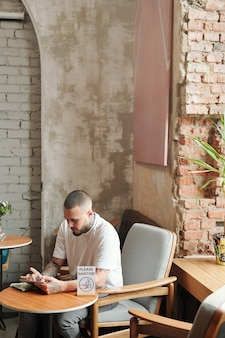 Nowoczesny wytatuowany facet siedzi przy małym stoliku w holu na poddaszu i korzysta z internetu na tablecie