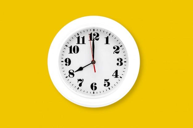 Nowoczesny zegar ścienny biały na białym tle na żółtym tle.