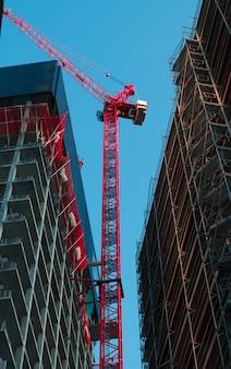 Nowoczesny żuraw budowlany na tle budynków w budowie