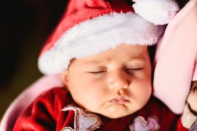 Nowonarodzona dziewczyna śpi z święty mikołaj kapeluszem