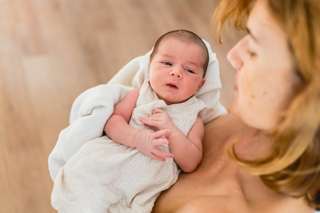 Nowonarodzona dziewczyna w kochających rękach jej matka