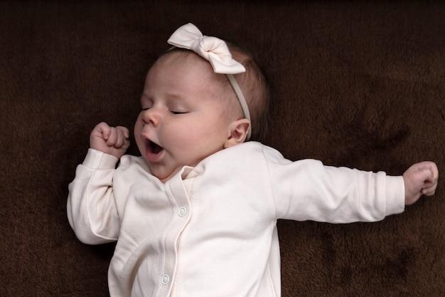 Nowonarodzona dziewczynka lub chłopiec chce spać, przeciera oczy ręką i ziewa