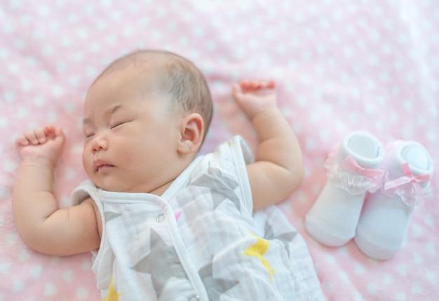 Nowonarodzona dziewczynka śpi na łóżku z skarpetą.