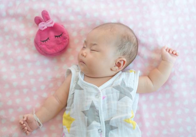 Nowonarodzona dziewczynka śpi na łóżku