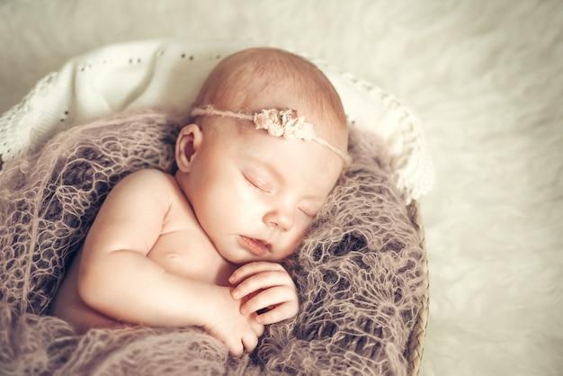 Nowonarodzona dziewczynka śpi w koszu. koncepcja fotografowania noworodków, niewinność
