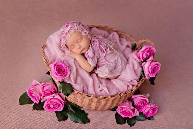 Nowonarodzona dziewczynka śpi w koszu retro z kwiatami różowych róż ogrodowych