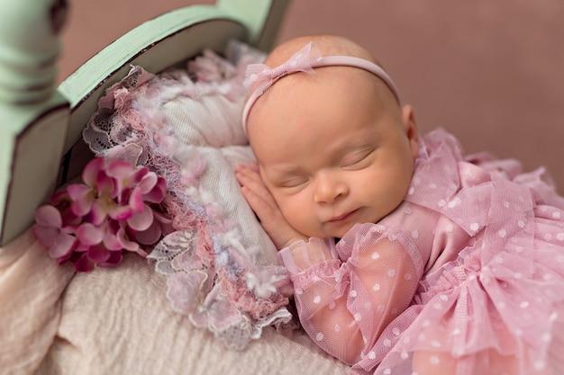 Nowonarodzona dziewczynka śpi w łóżku z różowymi kwiatami ogrodowymi