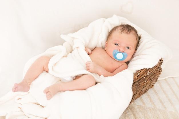 Nowonarodzony chłopiec leżący w starym wiklinowym koszu przykrytym kocem