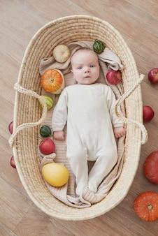 Nowonarodzony chłopiec leży w wiklinowej kołysce z dyniami i jabłkami. szczęśliwe macierzyństwo i ojcostwo. szpital i klinika położnicza. dzień ojca i matki. jesienne tło. święto dziękczynienia, halloween