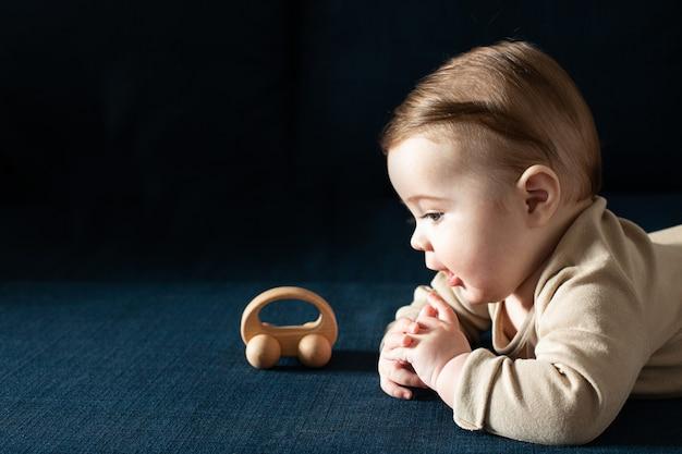 Nowonarodzony chłopiec maluch w beżowym body bawi się widokiem z boku drewnianej zabawki