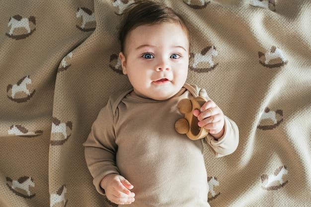 Nowonarodzony chłopiec maluch w beżowym body bawi się widokiem z góry drewnianą zabawką