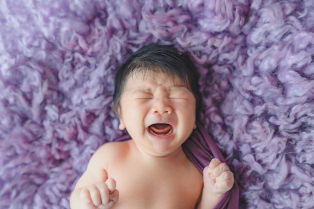 Nowonarodzony chłopiec płacze podczas snu na fioletowym futrzanym łóżku