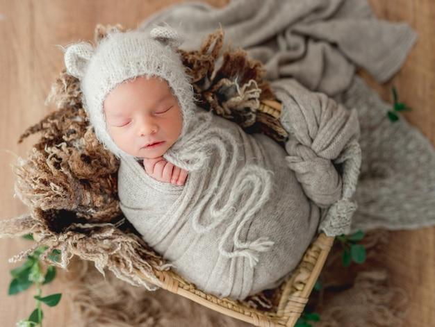 Nowonarodzony chłopiec śpiący otulony miękkim, dzianinowym kocem w uroczym wiklinowym koszu