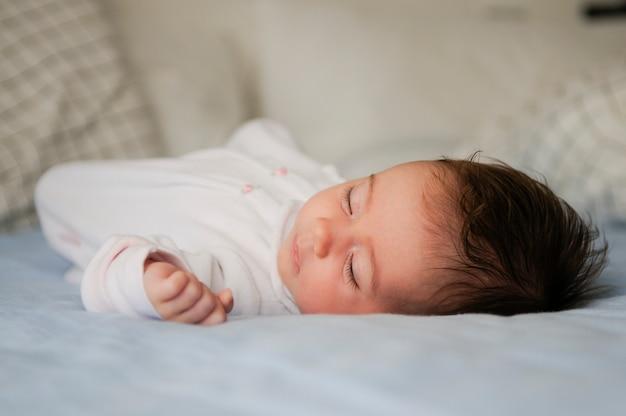 Nowonarodzony dziewczynki dosypianie na błękitnych prześcieradłach w domu