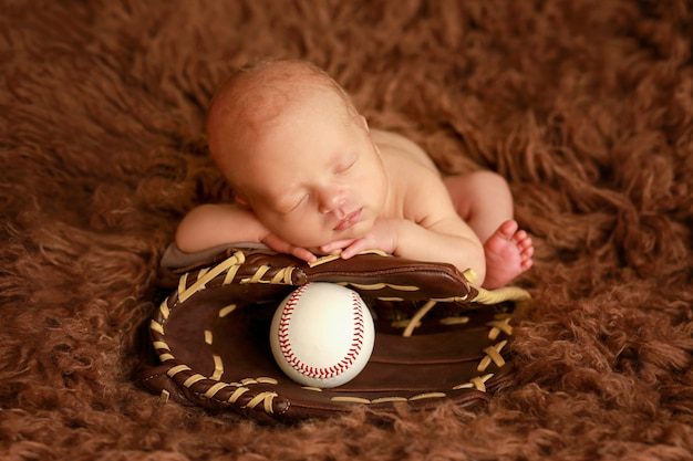 Nowonarodzony gracz baseballa. noworodek leży na rękawicy baseballowej z piłką do piłki. maluch z rękawicą i piłką. koncepcja gry w baseball.