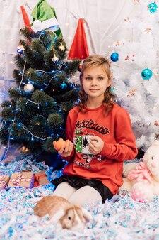 Noworoczna dziewczyna w świetlicy trzymająca filiżankę i mandarynki