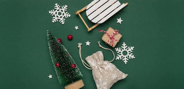 Noworoczna i świąteczna kompozycja z białych płatków śniegu, ozdobnej choinki i sań na zielonym tle papieru. widok z góry, kopia przestrzeń.