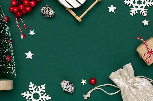 Noworoczna i świąteczna kompozycja z białych płatków śniegu, ozdobnej choinki i sanek, szyszek i czerwonych jagód na zielonym tle papieru. widok z góry, kopia przestrzeń, układ płaski.