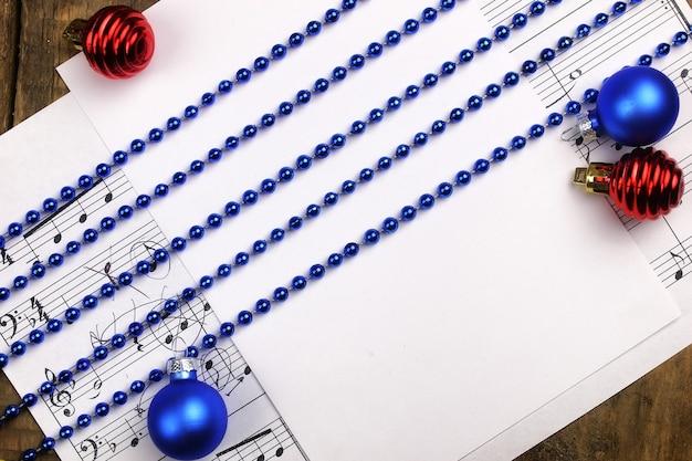Noworoczna kompozycja ozdoby choinkowe na stole i kartce z nutami