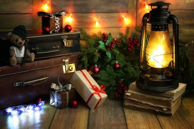 Noworoczna kompozycja z gałęzi choinek ozdobionych kulkami vintage lampa z płonącymi świecami i pudełkami wypełnionymi prezentami